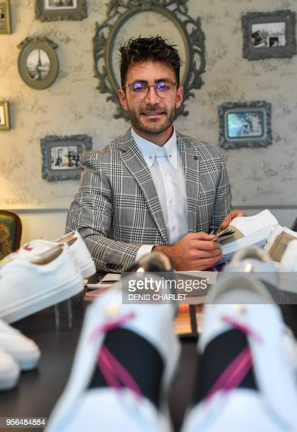 Syrian refugee Daniel Essa former TV presenter in Damas poses with the shoes he designed in Villeneuved'Ascq northern France on May 3 2018 Daniel...