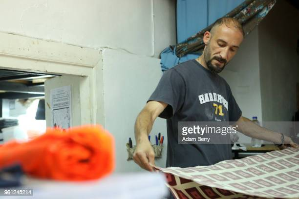 Syrian refugee Darwes Jalad prepares fabric to be sewn into life preserver material to make products to be sold at the Lesvos Solidarity...