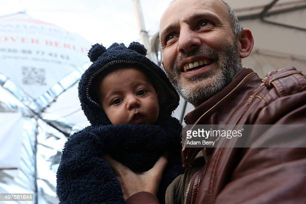 Syrian refugee Essam Martini holds his twomonthold son Yossef outside of an airdome used as a temporary shelter for refugees on September 26 2015 in...