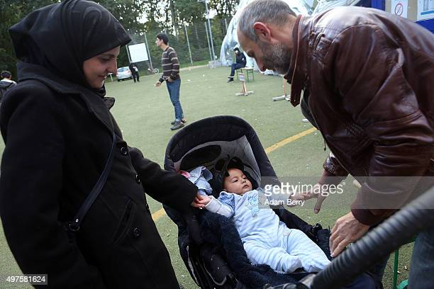 Syrian refugee Essam Martini prepares to hold his twomonthold son Yossef next to the child's mother outside of an airdome used as a temporary shelter...