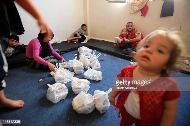 Syrian refugee familes receive meal packets from the UN's World Food Programme while staying in a temporary housing shelter on April 24 2012 near the...