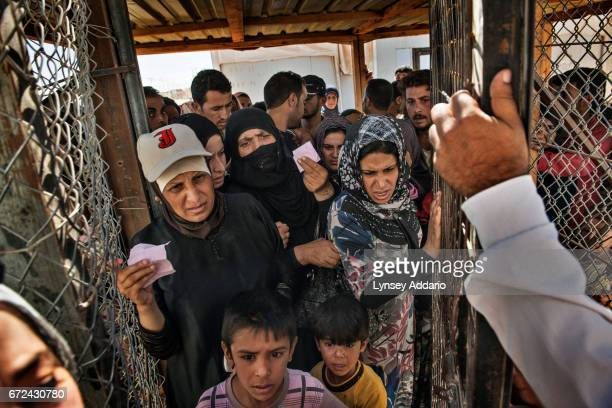 Syrian refugee families fight to pass through a gate to begin the registration process the morning after crossing into Jordan from Syria at the...