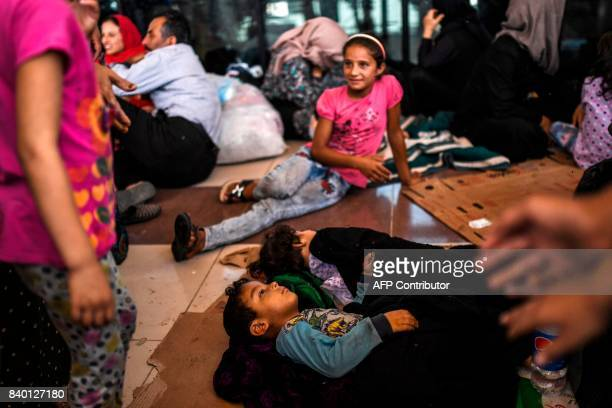 Syrian refugee families wait to register to cross to Syria for the Eid alAdha Muslim holiday on August 28 2017 at a bus station in the Turkish south...
