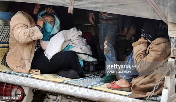 Syrian refugee families who have evacuated their homes due to shelling and bombardment by proregime forces sit in the back of a mini truck as they...