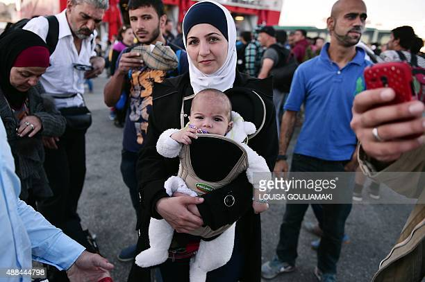 A Syrian refugee family disembarks at the port of Piraeus after arriving on a ferry from the Greek island of Kos on September 16 2015 Over half a...