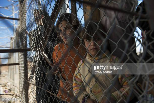 Syrian refugee family passes through a gate as they begin the registration process the morning after crossing into Jordan from Syria at the United...