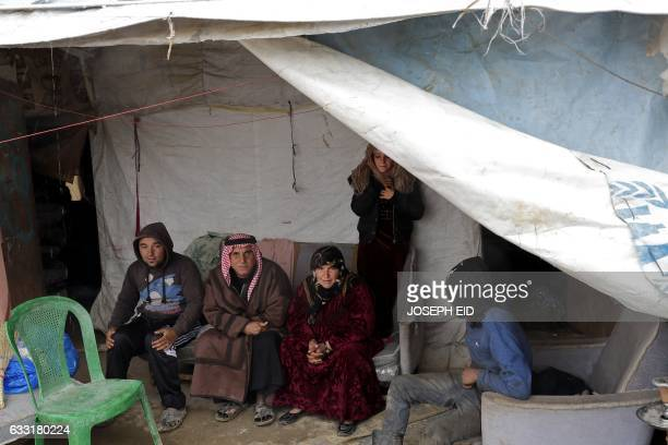 A Syrian refugee family sits at the entrance of their tent at an unofficial refugee camp in the village of Deir Zannoun in Lebanon's Bekaa valley on...