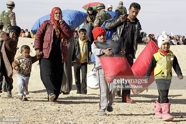 A Syrian refugee family walk with their belongings after crossing into Jordan at the Hadalat border crossing east of the Jordanian capital Amman on...