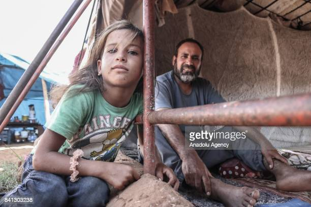 Syrian refugee girl and a man fled from Syrian city of Aleppo due to Assad Regime and Daesh terrorists' assaults are seen near the makeshift tents...