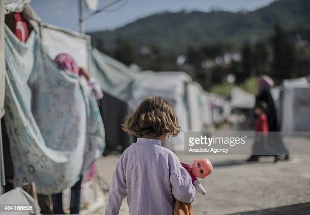 Syrian refugee girl fled from her home due to civil war walks with her toy in Yayladagi YIBO camp in Hatay province of Turkey on October 25 2015