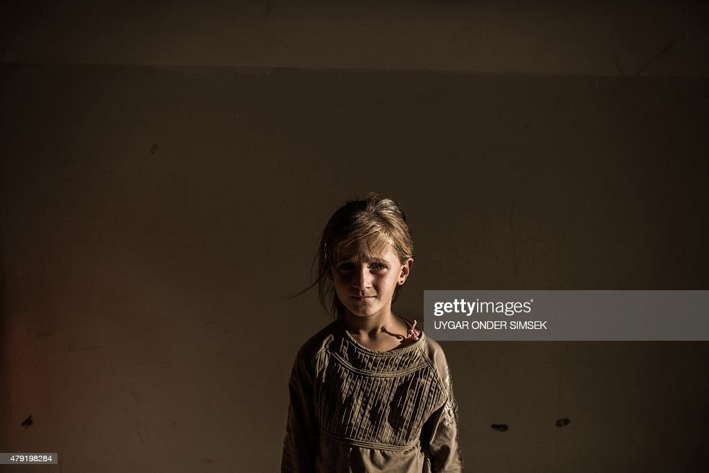 A Syrian refugee girl stands in a building on June 27, 2015 in Syrian Kurdish city of Amuda, after running away from clashes between regime forces and the Islamic State group.