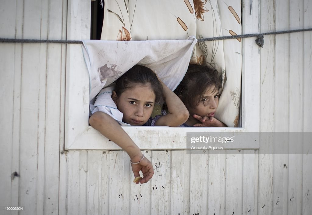 Syrian refugee girls are seen on the window of their prefabricated house at a tent city in the Akcakale District of Sanliurfa, Turkey on September 24, 2015. Turkish Red Crescent provided bank cards for the refugees and gives 85 Turkish Liras every month per person. 260 thousand Syrians who have escaped war and found asylum in Turkey are now living in camps with opportunities that mean they don't miss what they've left behind.