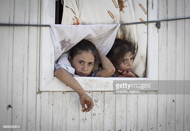 Syrian refugee girls are seen on the window of their prefabricated house at a tent city in the Akcakale District of Sanliurfa Turkey on September 24...