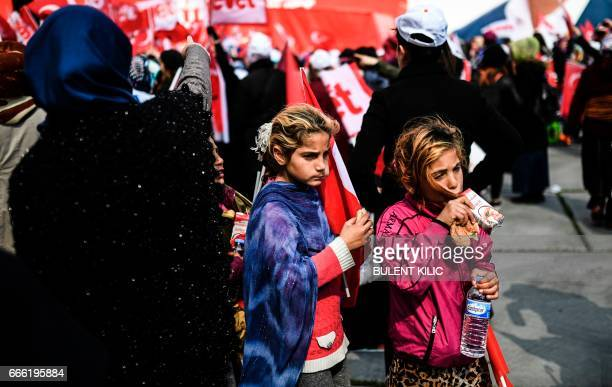 Syrian refugee girls eat a sandwich on April 8 2017 during a campaign rally for the 'yes' vote in a constitutional referendum in Istanbul On April 16...