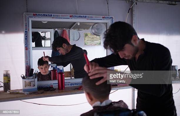 Syrian refugee has his hair cut in a barber shop at the Qushtapa Refugee Camp on December 14 2014 in Erbil Iraq Although the autonomous Kurdistan...