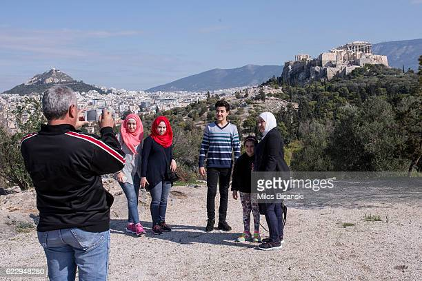 Syrian refugee Hassan Asaaid Alkhateb photographs his family in front of Acropolis Hill the day before travelling to Finland on October 30 2016 in...