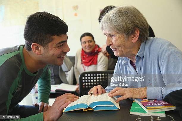 Syrian refugee Imad Awad chats with the help of a GermanArabic dictionary with a local volunteer at the biweekly 'Integration Cafe' gettogether at a...