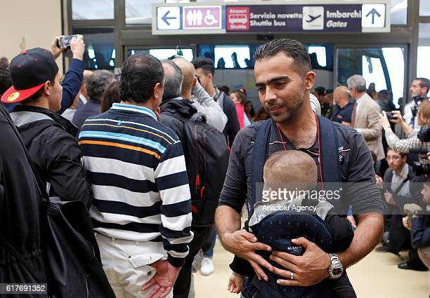 Syrian refugee keeping a baby in his arms arrives at Rome's Fiumicino international airport Italy on October 24 2016 About 70 refugees arrived from...