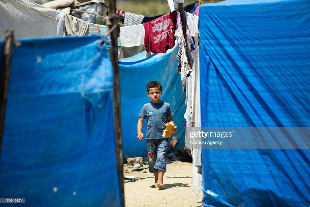 A Syrian refugee kid eats bread at a refugee camp in Adana, Turkey on July 06, 2015. Syrian refugees try to hold on life under harsh living conditions at a refugee camp in Koza neighborhood of Adana.