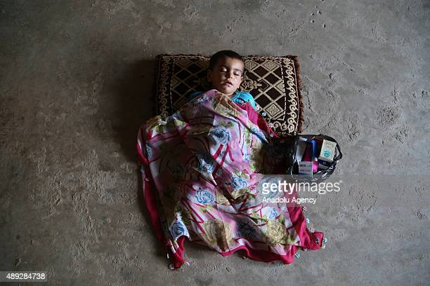 Syrian refugee kid sleeps on the ground of a house in Hatay province of southern Turkey on September 14, 2015. Syrian refugees who fled their country...