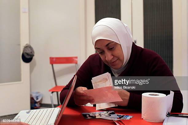 Syrian refugee Lama Asaaid Alkhateb looks at photos of her family's life before the war in Syria in her temporary Athens home on October 29 2016 in...