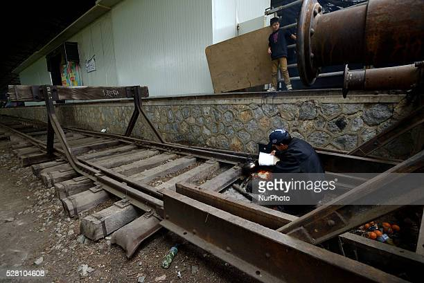 A Syrian refugee lights fire in an abandoned train station hangar at Idomeni refugee camp on May 3'rd 2016 Humanitarian conditions in the camp are...