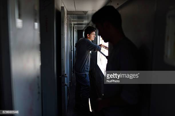 A syrian refugee looks through the window of an abandoned train cabin where he sleeps on May 6'th 2016 at Idomeni refugee camp Thousands of migrants...