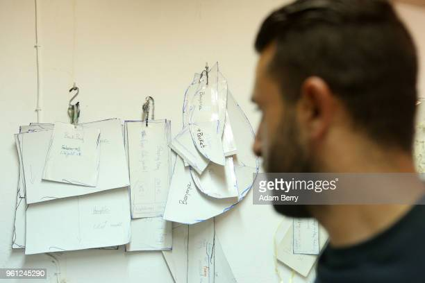 Syrian refugee Mahmoud Ibrahim looks at patterns to be sewn out of life preserver material to be sold at the Lesvos Solidarity organization's Safe...
