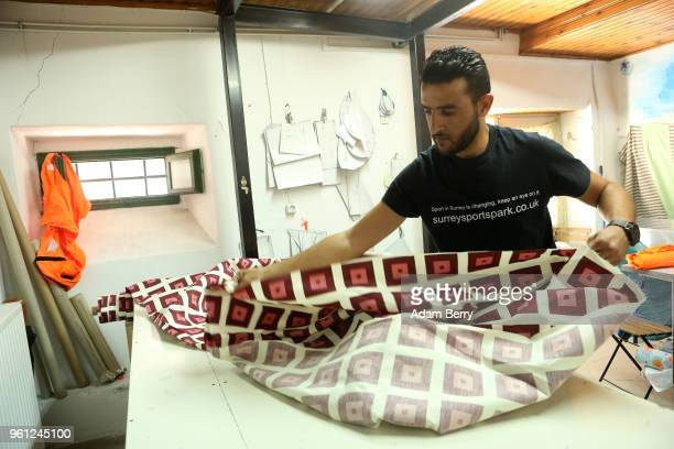 Syrian refugee Mahmoud Ibrahim prepares fabric to be sewn onto life preserver material to make products to be sold at the Lesvos Solidarity...