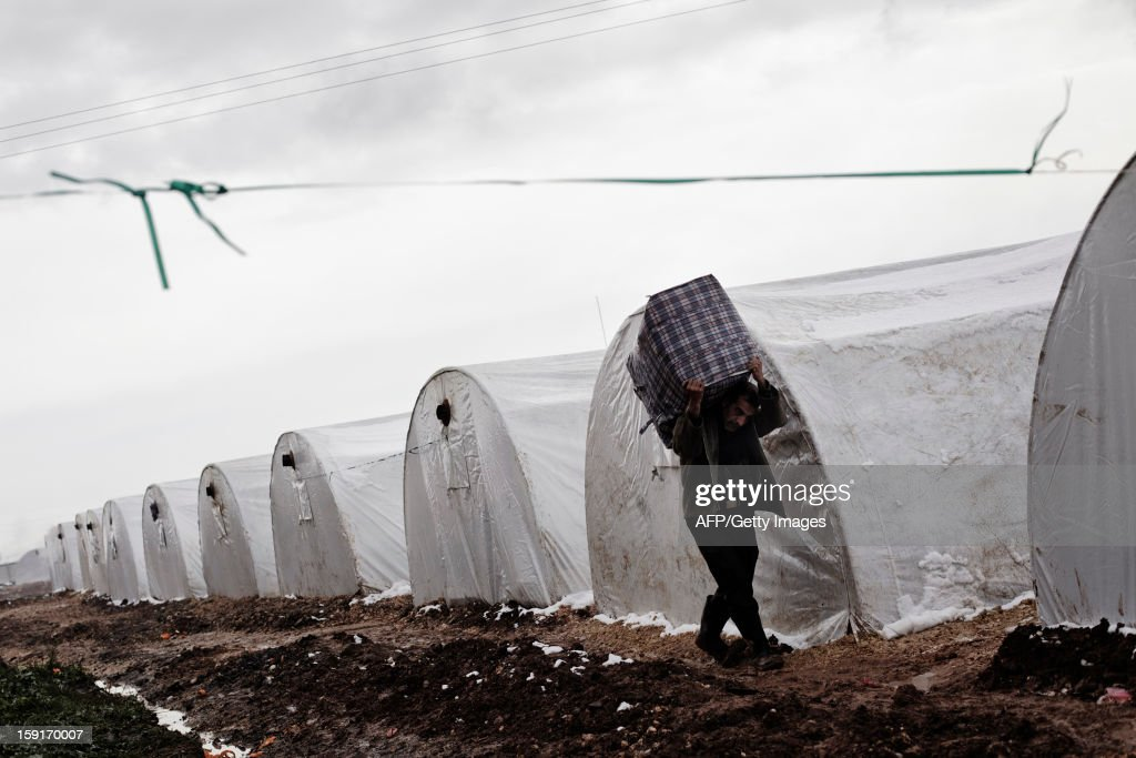 A Syrian refugee man carries a bag at a refugee camp near the northern city of Azaz on the Syria-Turkey border, on January 9, 2013. The internally displaced Syrians faced further misery due to increasing shortage of supplies as heavy rain was followed by a drop in temperatures.