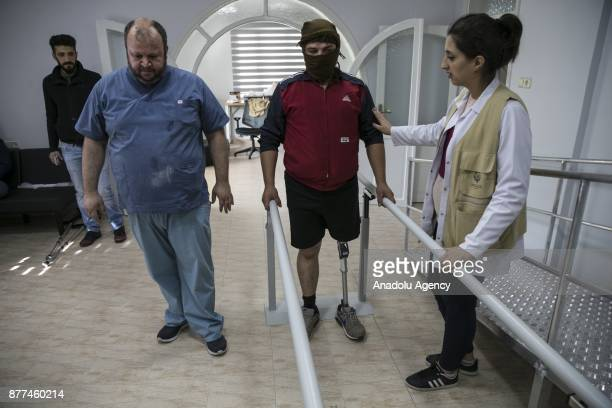 Syrian refugee man fled from Syria's Aleppo due to ongoing civilwar holds the fences as he receives physiotherapy at a medical center in Turkey's...