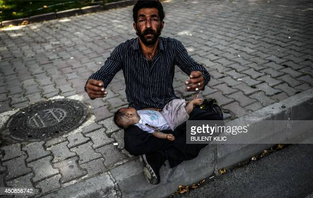 A Syrian refugee man gestures as he begs in the street with a baby lying on his lap in Istanbul on June 19 2014 Syria's army on June 15 said it had...