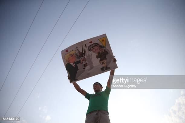 Syrian refugee man hold a banner which depicts US President Donald Trump and a PYD terrorist during a protest against PKK/PYD terrorist organization...