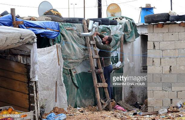 Syrian refugee man installs a makeshift heating system outside his tent in a camp in the village of Kfarkahel, in the Kura district near the northern...
