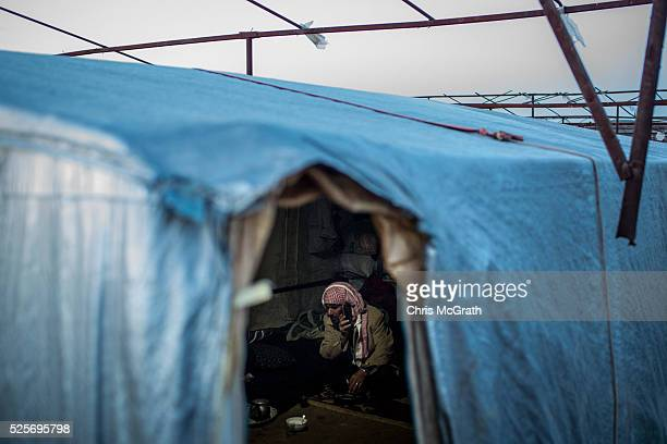 Syrian refugee man speaks on the phone inside his home at a tent camp on the outskirts of Izmir on April 28 2016 in Izmir Turkey For many Syrian...