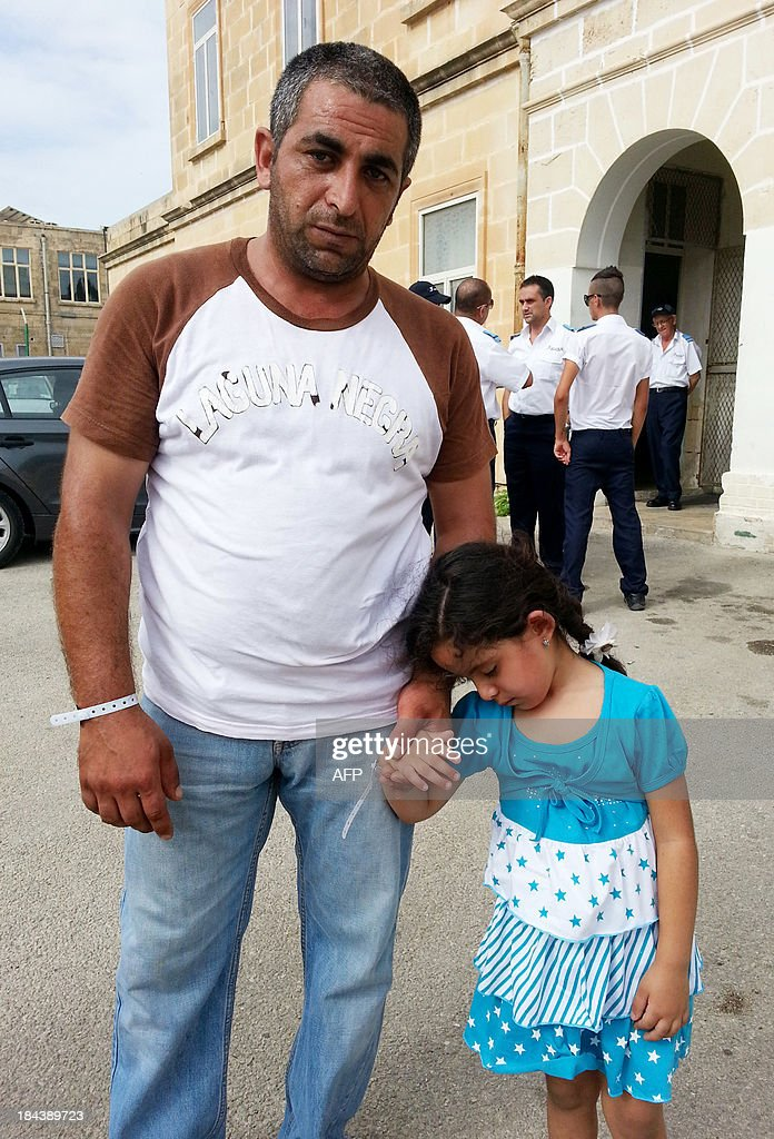 Syrian refugee Mohammed, 34, and his five-year-old daughter, pose in Valletta, on the Mediterranean island of Malta, on October 13, 2013. Syrian refugees who survived after their boat capsized off Malta in the latest disaster in the Mediterranean say they were fired on by warring trafficking gangs as they set out on their perilous journey from Libya.