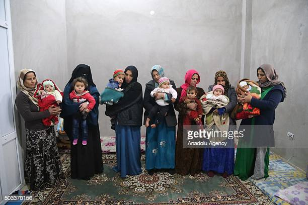 Syrian refugee mothers pose with their infants in a house in Reyhanli district of Hatay Turkey on January 4 2016 Syrian refugee families who have...