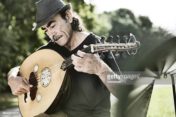 Syrian refugee playing Arabian lute oud