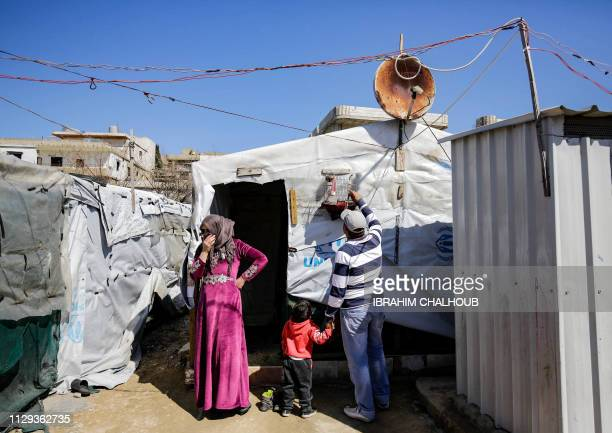 A Syrian refugee plays with his pet bird at a refugee camp in the village of Mhammara in the northern Lebanese Akkar region on March 9 2019