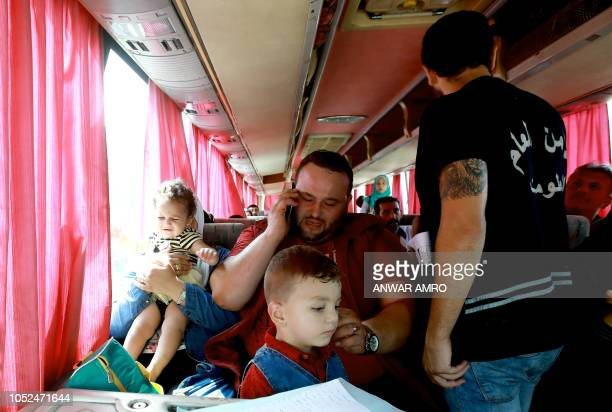 Syrian refugee Rawad Kurdi sits with his wife and children inside a bus on September 17 2018 as they return to Syrian after living as refugees in...
