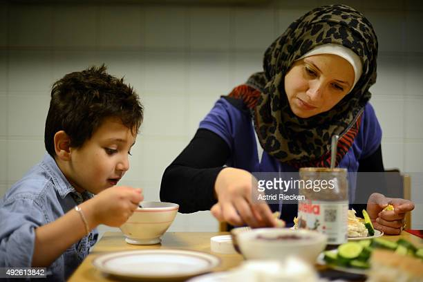Syrian refugee Reem Haskour and her son Ali AlAwis have breakfast at the community center of the Kreuzkirche where they now live October 7 2015 in...