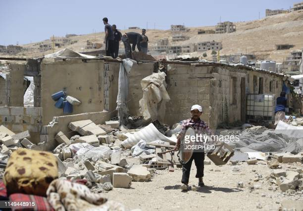 A Syrian refugee removes his belongings from a shack before it is demolished at a refugee camp in the northeastern Lebanese town of Arsal in the...