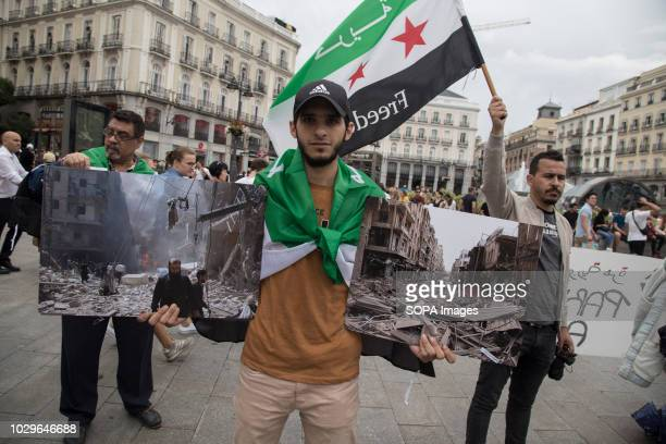 Syrian refugee seen with photos of the war during the protest in support of the Syrian revolution and against Bashar alÀssad demanding the release of...