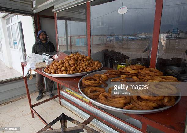 Syrian refugee stands outside a bakery at the Qushtapa Refugee Camp on December 14 2014 in Erbil Iraq Although the autonomous Kurdistan region of...