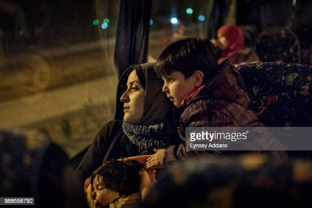 Syrian refugee Tayma Abzali sits with her two children baby Helen 4 months old and Wael 3 years old as they ride the bus with other refugee families...