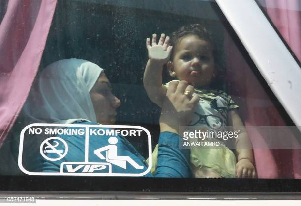 Syrian refugee Umm Luay sits with her child inside a bus on September 17 2018 she return with her family to Syrian after living as refugees in...