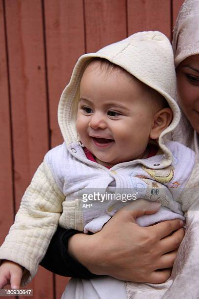 Syrian refugee Walaa Al Hodl holds her sixmonthold girl Nour on September 17 2013 at the Migrationsverket's facility in Marsta Sigtuna Sweden a...