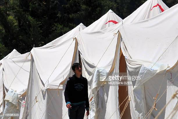 A Syrian refugee walks beside tents at the Turkish Red Crescent camp in the Yayladagi district of Turkey close to the city of Hatay two kms from the...