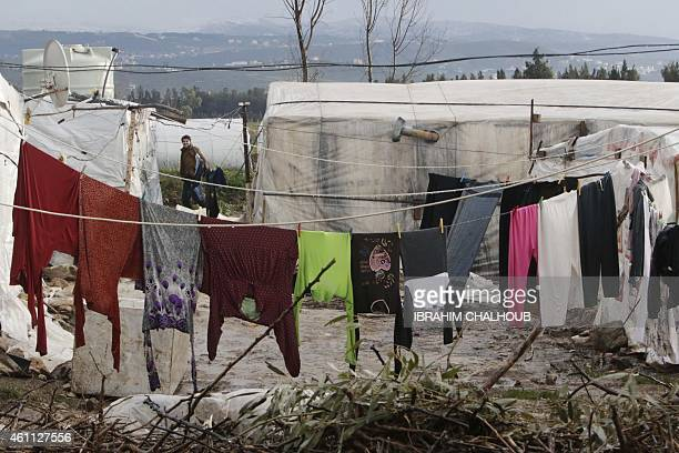 A Syrian refugee walks past temporary shelters at a refugee camp damaged by a winter storm in Akkara remote province of north Lebanon on January 7...