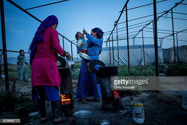 Syrian refugee woman feeds her child at a tent camp on the outskirts of Izmir on April 28 2016 in Izmir Turkey For many Syrian refugees living in...